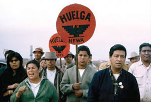 Cesar Chavez with activists holding signs that say Huelga